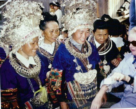 In Zhanao village, China showing a photograph to women dressed to dance in the Long Skirt Miao Festival of Ancestral Worship in 1997.