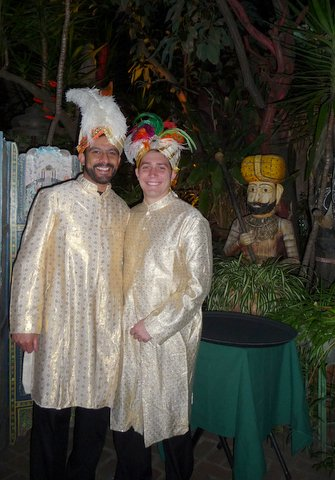 Two of the young servers next to the Indian carvings at night.