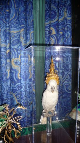 A stuffed white Cockatoo wearing a miniature Thai dancer's headdress observes the party guests